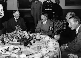 Undated Photo of Adolf Hitler at a banquet table.  No doubt his taster has approved his meal and will live to see another day (maybe) (Photo Credit:  huffingtonpost.com)