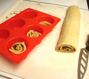 """After rolling, slice the roll into 1"""" """"snails"""" and place into prepared microwave safe muffin pans"""