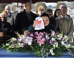 This distraught lady is evidently fulfilling the deceased's last wishes (Photo Credit: www.nydailnews.com)